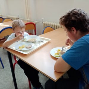 Prvňák s deváťákem u stolu v jídelně